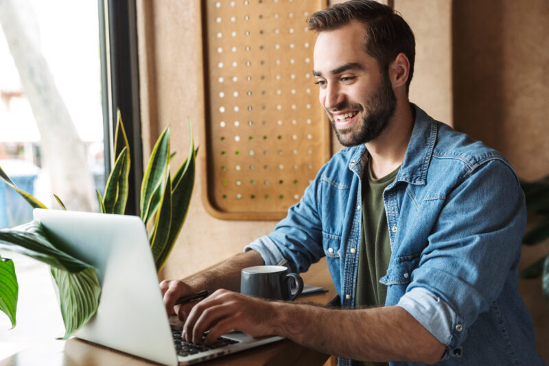 Photo of smiling european man wearing denim shirt typing on laptop with cup of coffee while working in cafe indoors