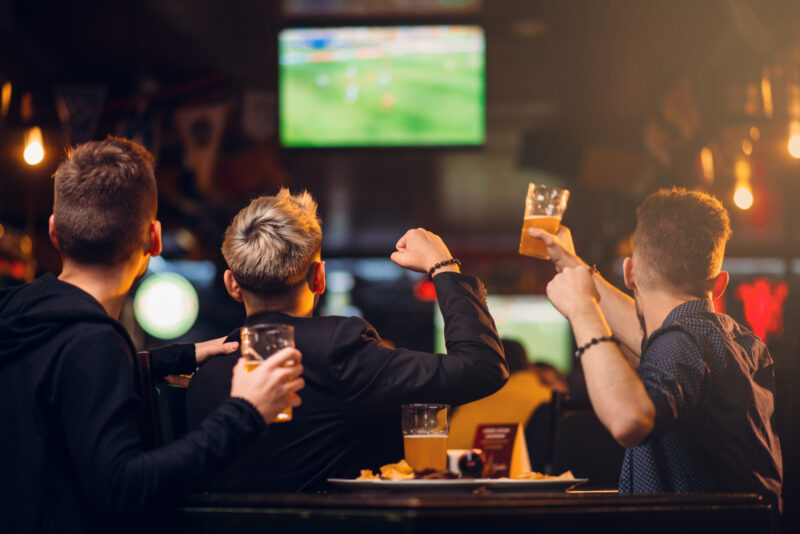 Three men watches football on TV in a sport bar, happy leisure of fan company